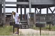 Photo shows a gentleman using one of the grills at one of the beach use area pavilions.