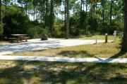 View from the right showing ADA picnic table and ground grill along with vegetation buffering the campsite.