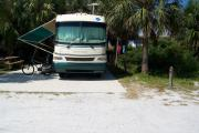 View from the front showing a RV parked with the awning fully extended and the water hookup and electrical box on the right.