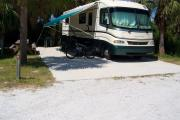 View from the front showing the RV parked on the concrete slab and the picnic table on the left.