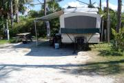 View from the front showing the RV hooked up to the water and electric on the right and picnic table on the left.