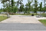 ADA-accessible campsite with concrete pad, picnic table, cooking grill with electric and water in a campsite with view of lake.