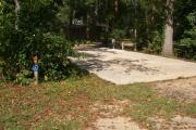 ADA-accessible campsite with concrete pad with electric and water in a campsite with restroom.
