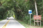 A motorcyclist cruises thru the tunnel of trees on the Ormond Scenic Loop and Trail, a designated Florida Scenic Highway that meanders thru the Tomoka Basin State Parks.