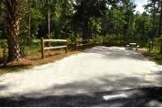 Campsite #1 at Wekiwa Springs State Park has a crushed shell surface and is surrounded by sections of split rail fence and trees creating partial shade on the site.  A picnic table and in-ground fire ring/grill are provided on the site along with water and 30amp electrical service.