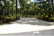 Campsite #3 at Wekiwa Springs State Park has a crushed shell surface and is surrounded by sections of split rail fence and trees creating partial shade on the site.  A picnic table and in-ground fire ring/grill are provided on the site along with water and 30amp electrical service.