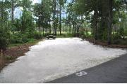 Campsite #8 at Wekiwa Springs State Park has a crushed shell surface and is surrounded by sections of split rail fence and trees creating partial shade on the site.  A picnic table and in-ground fire ring/grill are provided on the site along with water and 30amp electrical service.