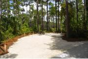 Campsite #9 at Wekiwa Springs State Park has a crushed shell surface and is surrounded by sections of split rail fence and tall Pines creating partial shade on the site.  A picnic table and in-ground fire ring/grill are provided on the site along with water and 30amp electrical service.