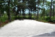 Campsite #11 at Wekiwa Springs State Park has a crushed shell surface and is surrounded by sections of split rail fence and trees creating partial shade on the site.  A picnic table and in-ground fire ring/grill are provided on the site along with water and 30amp electrical service.