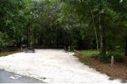 Campsite #13 at Wekiwa Springs State Park has a crushed shell surface and is surrounded by sections of split rail fence and trees creating partial shade on the site.  A picnic table and in-ground fire ring/grill are provided on the site along with water and 30amp electrical service.