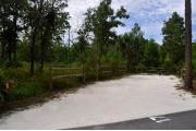 Campsite #17 at Wekiwa Springs State Park has a crushed shell surface and is surrounded by sections of split rail fence and trees creating partial shade on the site.  A picnic table and in-ground fire ring/grill are provided on the site along with water and 30amp electrical service.