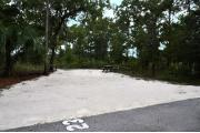 Campsite #23 at Wekiwa Springs State Park has a crushed shell surface and is surrounded by sections of split rail fence and trees creating partial shade on the site.  A picnic table and in-ground fire ring/grill are provided on the site along with water and 30amp electrical service.
