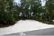 Campsite #24 at Wekiwa Springs State Park has a crushed shell surface and is surrounded by sections of split rail fence and trees creating partial shade on the site.  A picnic table and in-ground fire ring/grill are provided on the site along with water and 30amp electrical service.