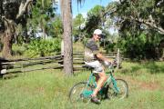 A Lake Kissimmee State Park visitor cruising on his teal colored bicycle through the pine trees.