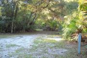 36x34 foot shell rock camp site with water and electric hook ups surrounded by saw palmetto.