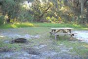 Picnic table and fire pit/grill in grass on side of shell rock pad shaded under an oak tree.