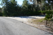 In LOOP 1 #23, a better view of the entrance to the site more palmetto and trees surround the site. Site Marker is on the right side of the main road