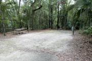 A September view of the picnic table and lantern post for hanging your lantern on left and electrical hookup on right, from within campsite #7.  Site is surrounded on three sides by a mixed oak, pine, and cabbage palm forest.  A RV on an adjacent site is visible through the woods, behind the picnic table.