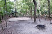 A September view of tent site #19, showing raised tent pad, with fire ring in foreground, water and electrical hookups to the right, and picnic table on right edge of picture. Site is surrounded on three sides by a mixed oak, pine, and cabbage palm forest.