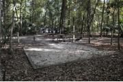 A September view of tent site #22, showing raised tent pad, fire ring, water and electrical hookups and picnic table.  Walkway to tent sites is seen in background, and parking for tent sites is seen through woods in far background.  Site is surrounded on three sides by a mixed oak, pine, and cabbage palm forest.