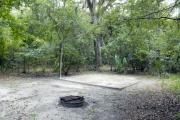 A September view of tent site #24, showing raised tent pad, with fire ring in foreground, and lantern post for your lantern.   Water and electrical hookups are a short distance away.  Site is surrounded on three sides by a mixed oak, pine, and cabbage palm forest.