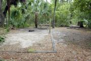 A September view of tent site #29, showing raised tent pad, fire ring, picnic table and lantern post.  Water and electrical hookups are a short distance away.  Site is surrounded on three sides by a mixed oak, pine, and cabbage palm forest.