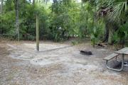 A September view of tent site #29, showing raised tent pad, fire ring, picnic table and lantern post.  Water and electrical hookups are a short distance away.  Site is surrounded on three sides by a mixed oak, pine, and cabbage palm forest. Campground loop drive is visible through woods on right.