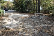 A September view from within campsite #40.  The picnic table, fire ring, and grill are seen on right.  Site is surrounded on three sides by a mixed oak, pine, and cabbage palm forest.  Across the campground drive, a truck is parked at the nearby bathhouse.