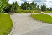 A 65 feet long gravel pull through campsite with vegetation giving privacy to the left. The sitting area is also located on the left and has a wooden picnic table and a cast-iron fire circle. Water and electric hook-ups are on the right hand side of the site.
