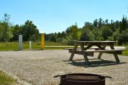 A fire circle and a picnic table in the foreground with the neighboring campsite across the road.