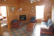 A nice shot of the living room showing the couch, two chairs and a table as well as the propane powered fireplace. The cabins are tiled throughout.