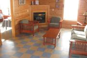 A nice picture of the living room showing the couch, two chairs and a table as well as the propane powered fireplace. The cabins are tiled throughout.