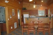 View showing the dining room with a large wooden table, kitchen with modern appliances and part of the bathroom.