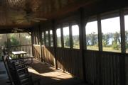 A large screened porch with single and double rocking chairs. The porch also has 2 ceiling fans for your comfort.