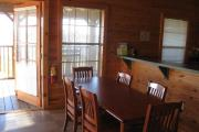 French doors lead from the screened in front porch to the kitchen and dining room. The rustic wood dining table seats 6.