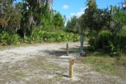 Looking at campsite marker #9; site mostly sunny in afternoon; water spigot and electrical hook up on right