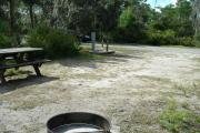 Looking out of site toward campground road; picnic table, water spigot and electrical hook up on left; fire ring on left; site mostly sunny in afternoon
