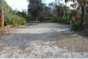 Looking into site from campground road; site mostly grass and sand; water spigot and electrical hook up on right; picnic table and fire ring at rear of site
