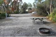 Looking out of site toward campground road; site is mostly grass and sand; water spigot and electrical hook up on left; fire ring and picnic table at rear of site
