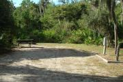 Looking into site from campground road; water spigot and electrical hook up on right; picnic table and fire ring on left; site mixture of grass and sand