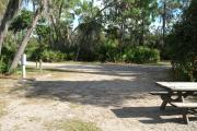 Looking out of site toward campground road; fire ring and picnic table on right; water spigot and electrical on left; site mixture of grass and sand, partially shaded