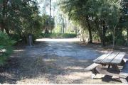 Looking out of site, toward campground road; picnic table is on right; fire ring, water spigot, and electrical hook up are on the left; site is mostly shaded in morning