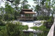 A tranquil moment at a pavilion with canoes, a boardwalk, and glass-like water at Big Lagoon State Park.