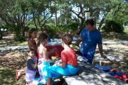 A family in brightly colored clothing enjoying a snack in the shade on a picnic table at Big Lagoon State Park.