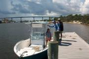 Three adults in the bright sunshine preparing to board a boat at Big Lagoon State Park's boat launch on the still waters of the Intracoastal Waterway.