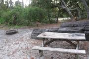 View of a wooden retaining wall, picnic table and fire ring in shade.