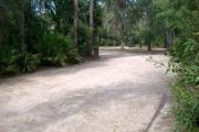 View of a vacant campsite with a fire ring/grill and picnic table. The main part of the site is sandy with sparse vegetation and a mix of trees to the sides. There is partial shade.
