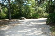 View of a vacant campsite with a picnic table, a fire ring/grill, electric pedestal, and water spigot. There is a large oak tree which provides partial shade.