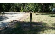 This picture shows the numbered post for campsite 18 which is a 69 foot pull through site. There is a wooden table and a ground fire ring/grill in the background. In the left corner is the electric and water hook ups. It is an open site with grassy areas, saw palmettos and a small magnolia to the right.