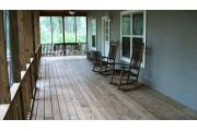 This picture of cabin 2 is taken where the screened in porch makes an L. The porch is L shaped and runs the full length of both sides of the cabin. The porch has a wooden picnic table, chairs and a swing for your use as pictured. The porch has two access doors, one from the kitchen and the other is on the back side (other part of L shaped porch) between the fireplace and bedroom walls.